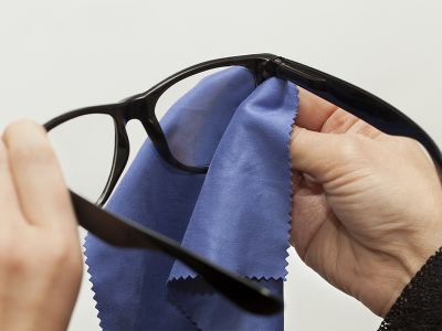 Eyeglasses are a financial investment and it's important to take proper care of them. Unfortunately, many people don't take the time to clean glasses properly—opting instead to use the sleeve of a shirt or any nearby cloth. In order to keep your glasses scratch-free, follow our eyeglass cleaning tips! Use a Lens Cloth Always use a dedicated lens or microfiber cloth to clean lenses. Other clothes can have dirt and small particles on them that can cause scratches or other abrasions on lenses. Never Use Household Glass Cleaner You may be tempted to use the cleaner that you use for windows and mirrors on your lenses—but you shouldn't. These cleaners often contain ammonia that can damage your glasses. Only use eyeglass cleaner or warm water with a bit of dish soap. Clean Often Ensure that you clean your glasses regularly to prevent a buildup of oil and dirt—ideally at least once a day. This buildup can make it difficult to see and can cause symptoms of eyestrain. If your glasses have nose pads, make sure you take some extra time to thoroughly clean them. Store Properly It's also important to store glasses correctly. When not in use, put glasses in a case to protect them and keep them dust free. It's also a good idea to keep a soft microfiber cloth in your glasses case for the quick cleanup of smudges while you're on the go.